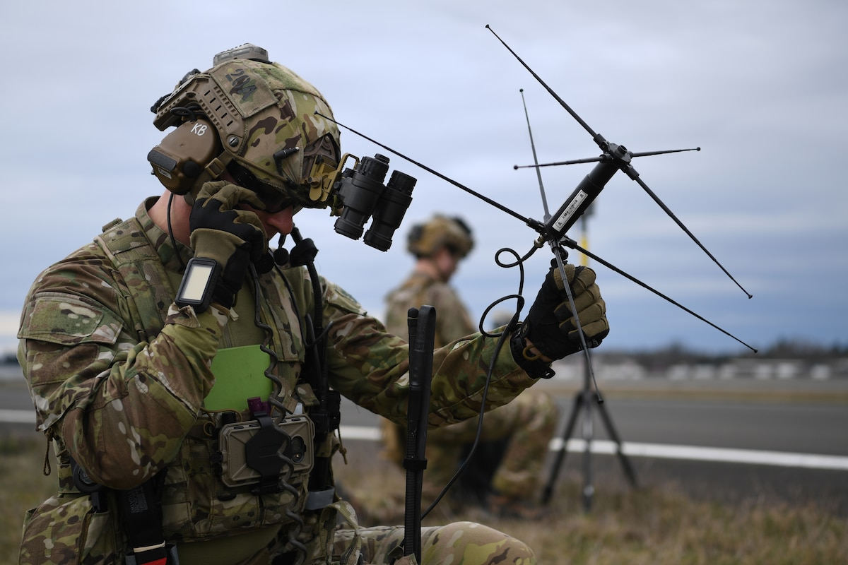 Two airmen hold communication devices,