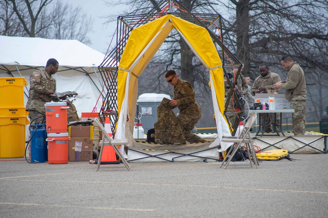 Airman set up a tent and tables.