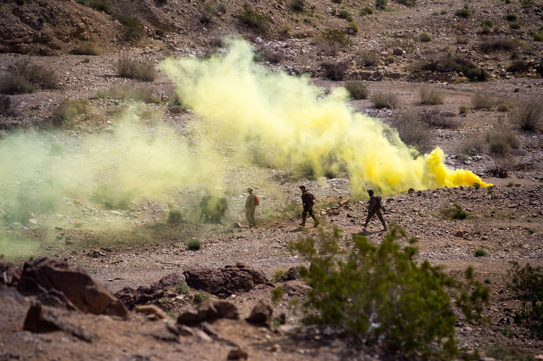 A group of Marines walk across a desert landscape while yellow smoke billows from behind them.