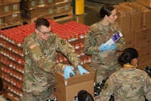 Soldiers of the California Army National Guard's 115th Regional Support Group work with civilian volunteers and diligently pack food and produce March 21 at the Sacramento Food Bank & Family Service in Sacramento, California. California Guardsmen were activated to assist the state during the recent COVID-19 outbreak. (Army National Guard photo by Staff Sgt. Eddie Siguenza)