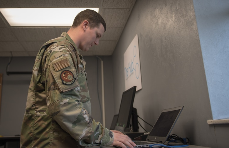 """Tech. Sgt. Jessica Oliver, 2nd Communications Squadron base equipment control office NCO-in-charge, looks over an inventory of laptops ready for customer use at  Barksdale Air Force Base, La., March 20, 2020. To meet the surge of teleworking personnel, the 2nd CS expanded operations of """"The Hub,"""" a walk-in computer clinic, by repurposing a conference room as a laptop porting station. (U.S. Air Force photo by Tech. Sgt. Daniel Martinez)"""