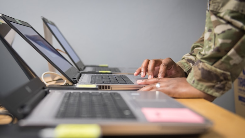"""Staff Sgt. Kendall Armand, 2nd Communications Squadron client systems supervisor, looks over a laptop as it's being reimaged at Barksdale Air Force Base, La., March 20, 2020. Armand works at """"The Hub,"""" a walk-in computer clinic where Airmen from the 2nd CS work to install and fix various computer software issues. (U.S. Air Force photo by Tech. Sgt. Daniel Martinez)"""