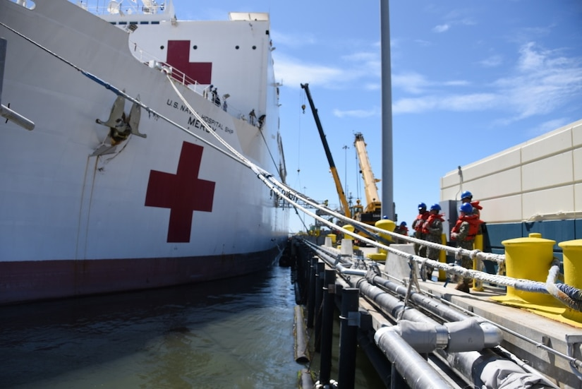Sailors wearing blue helmets work beside a docked ship marked with red crosses.