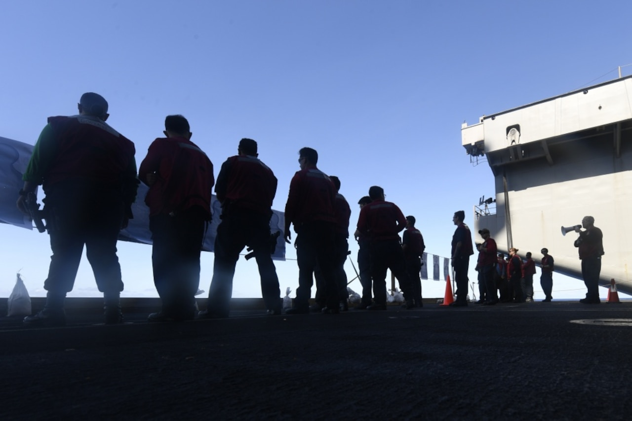 Sailors stand on aircraft carrier deck.