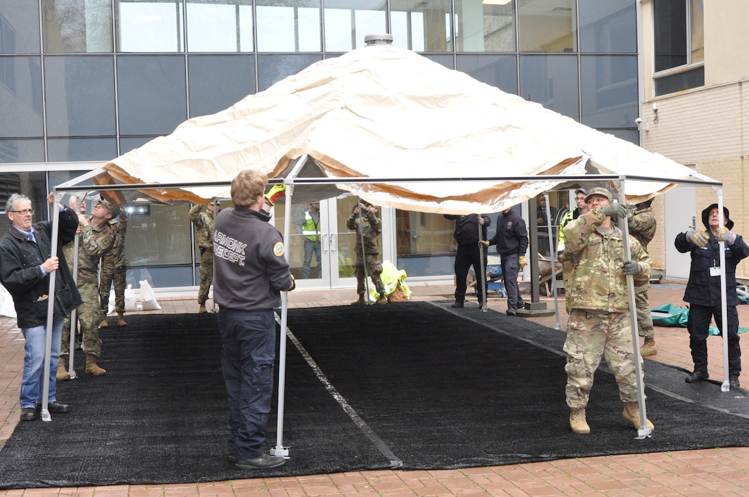Soldiers and civilians put up a tent near an office building.