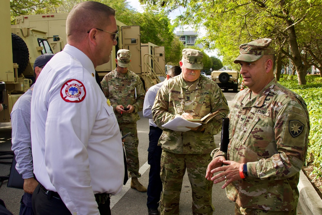 A soldier talks with a member of the fire department while standing outside near military vehicles.