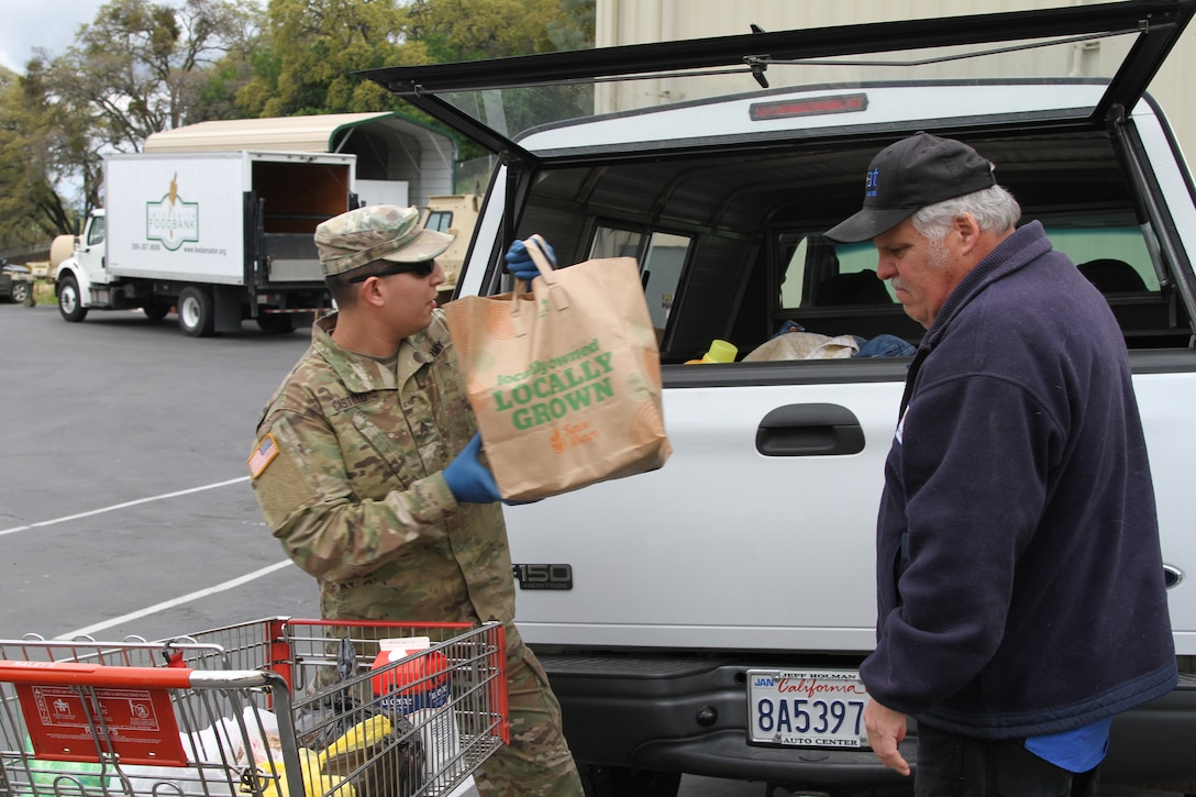 A soldier loads groceries into the back of a truck while an older man stands nearby.