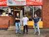 One man in black shirt with blue jeans and black shoes stands with crossed arms, next to man in white t-shirt and black pants with thumbs up, and a third man in blue shirt with red lettering and blue jeans stands with hands on hips in front of a brick building that has a pizza shop sign.