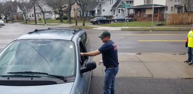 Man in blue shirt, blue jeans, and blue hat with white gloves on hands a bag to driver of grey van sitting in a parking lot.