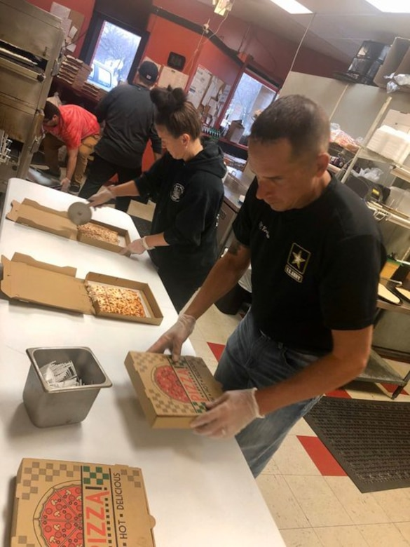 Man in black shirt, blue jeans and white gloves holds pizza box, while woman in black shirt cuts pizza in box.