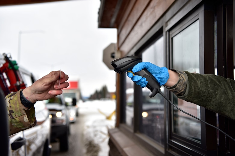 A 354th Security Forces Squadron Airman scans a common access card on Eielson Air Force Base, Alaska, March 20, 2020. Installation personnel and visitors must present their I.D. to defenders at the main gate for verification. The change is one of many precautionary measures implemented base-wide to help prevent the spread of COVID-19. (U.S. Air Force photo by Senior Airman Beaux Hebert)