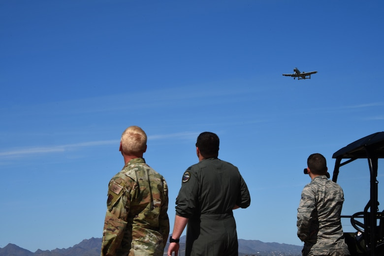 a photo of Airmen watching an A-10 fly over