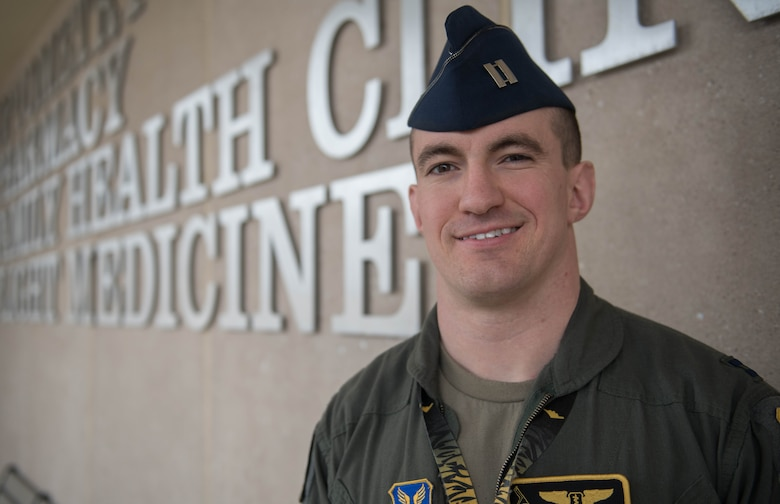 """Air Force Capt. (Dr.) Joseph Sharp, a 509th Medical Group flight surgeon, stands in front of the clinic at Whiteman Air Force Base, Missouri, March 1, 2020. Sharp earned the Air Force Global Strike Command """"Flight Surgeon of the Year Award"""" for his innovative practices and dedication to his patients. (U.S. Air Force Photo by Airman 1st Class Thomas Johns)"""