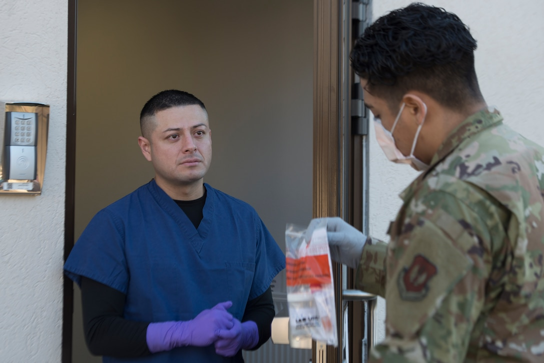 An Airman receives medical materials from a colleague.