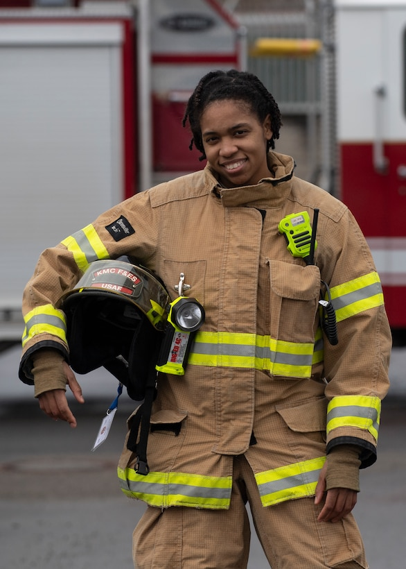 Photo of firefighter posing in gear in front of a fire truck