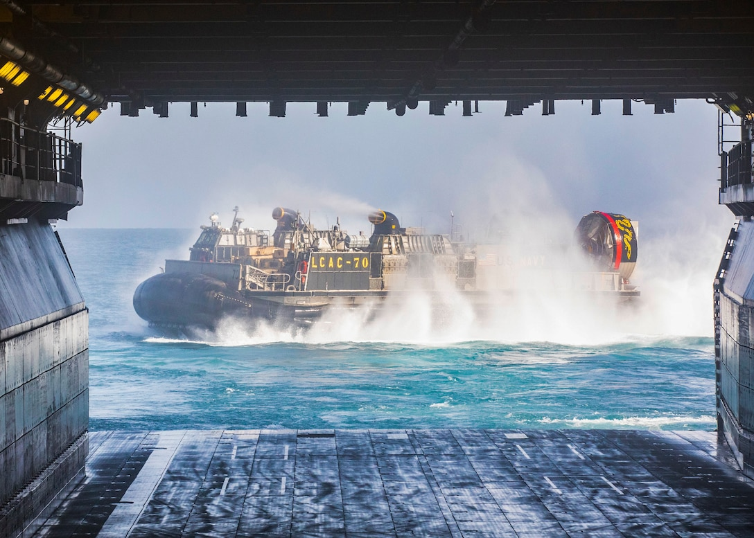 Landing Craft, Air Cushion 70, attached to Assault Craft Unit 4, departs from the well deck of the amphibious assault ship USS Bataan (LHD 5), March 19, 2020. Bataan is the flagship for the Bataan Amphibious Ready Group and, with the embarked 26th Marine Expeditionary Unit, is deployed to the U.S. 5th Fleet area of operations in support of naval operations to ensure maritime stability and security in the Central Region, connecting the Mediterranean and the Pacific through the Western Indian Ocean and three strategic choke points. (U.S. Navy photo by Mass Communication Specialist 3rd Class Alan L. Robertson)