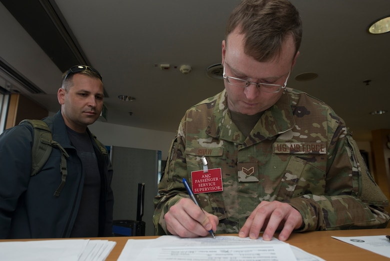 A picture of an Airman filing documents for a passenger.