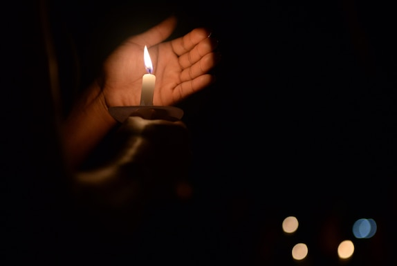 Photo shows a pair of hands shield a candle flame in a dark room.