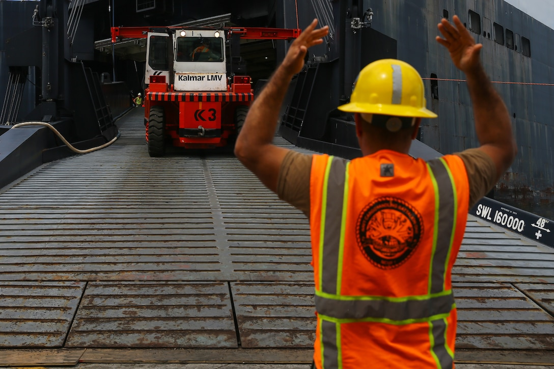 A U.S. Navy sailor ground guides a Kalmar Lidhults Mekaniska Verkstad container forklift truck down the ramp during a Maritime Prepositioning Force exercise at U.S. Naval Base Guam, Feb. 27.