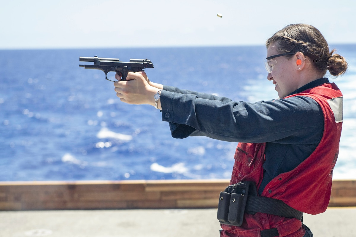 A sailor fires a weapon.