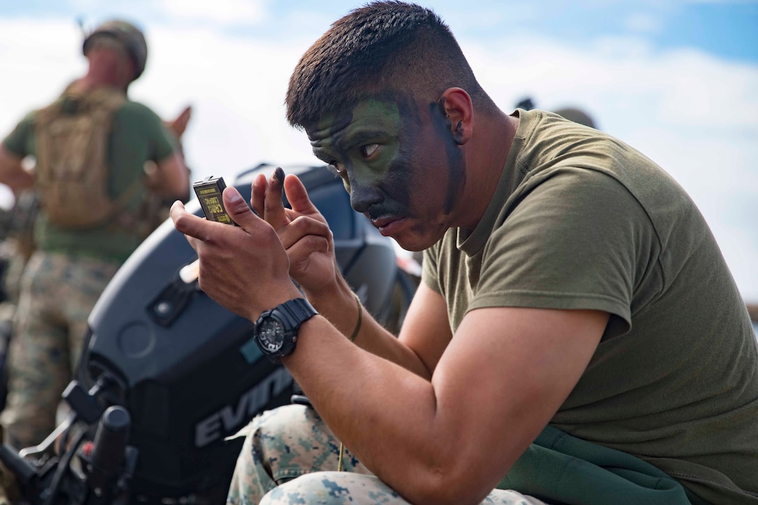 A Marine paints his face green and black while holding a small mirror.