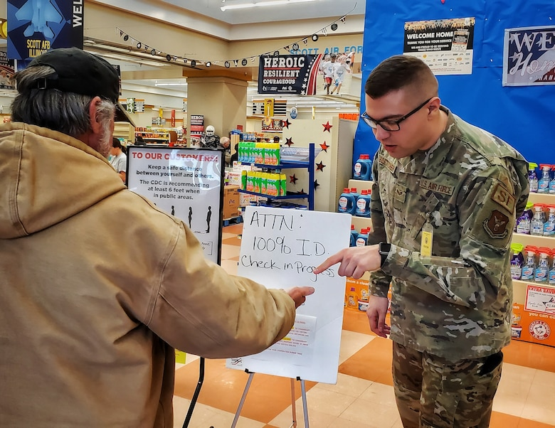 Senior Airman Austen Boettcher, from the 932nd Security Forces Squadron, volunteers to check IDs at the Scott Air Force Base commissary March 20, 2020. (U.S. Air Force photo by Christopher Parr)