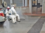 Street cleaners spray while wearing anti-virus suits.
