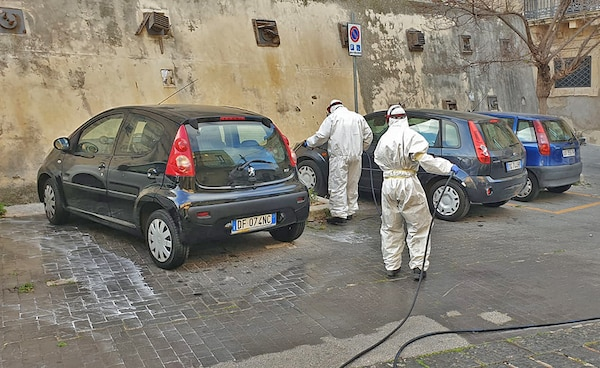 Volunteers in hazmat suits spray down cars in Sicily.