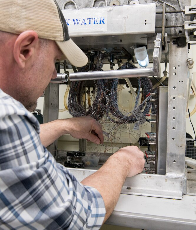 Brian Anderson, an instrumentation specialist, connects wires from a Schmidt-Boelter heat flux gauge to a machine used to calibrate the gauges Jan. 15, 2020, in the Aerothermal Calibration Laboratory at Arnold Air Force Base, Tenn. (U.S. Air Force photo by Jill Pickett)