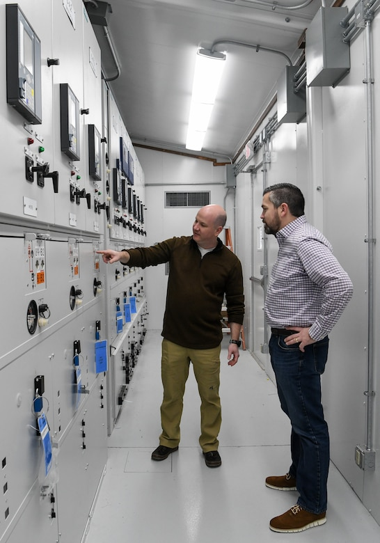 Tyler McCamey, left, an AEDC program manager, observes a gauge on gas-insulated switchgear (GIS) for the Propulsion Wind Tunnel (PWT) Facility, Feb. 14, 2020, at Arnold Air Force Base, Tenn. The switchgear was upgraded to GIS as a Service Life Extension Program effort. Also pictured, Nathan Harrison, former Service Life Extension Program manager for the Capital Improvements Branch. (U.S. Air Force photo by Jill Pickett)