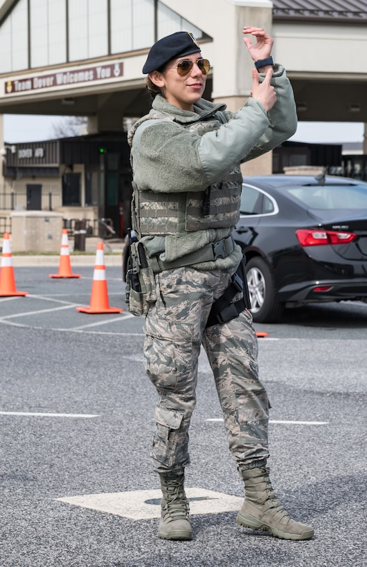 Airman 1st Class Glenda Heredia, 436th Security Forces Squadron response force leader, signals a vehicle driver to display their wristband prior to departing the screening area March 18, 2020, at the main gate on Dover Air Force Base, Delaware. Patrons destined for the base clinic were directed by 436th SFS personnel to a screening area attended by 436th Medical Group personnel prior to allowing them to proceed to the base clinic. Screening clinic patrons in their vehicle mitigates the possible transmission of COVID-19. (U.S. Air Force photo by Roland Balik)