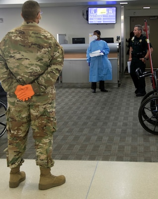 Florida National Guard Spc. Joe Morales-McCullers, 13th Army Band Miramar Fla., waits for passengers arriving from the New York area at Fort Lauderdale-Hollywood International Airport, March 25, 2020. The 13th Army Band is helping screen the passengers to slow the spread of the coronavirus.