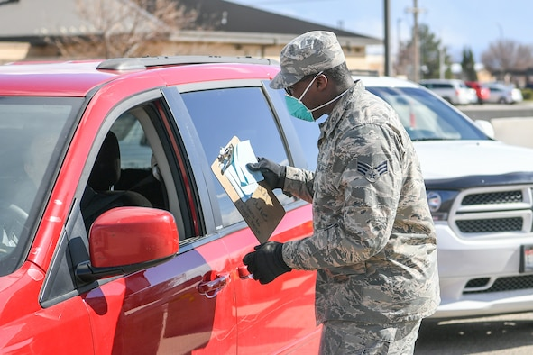 Senior Airman Elijah Thompkins, 75th Medical Group, consults with a beneficiary March 23, 2020, at Hill Air Force Base, Utah. The 75th Medical Group Satellite Pharmacy is providing curbside service until further notice in front of the Base Exchange shopping center in support of social distancing recommendations and to increase efforts to mitigate further spread of the novel coronavirus.(U.S. Air Force photo by Cynthia Griggs)