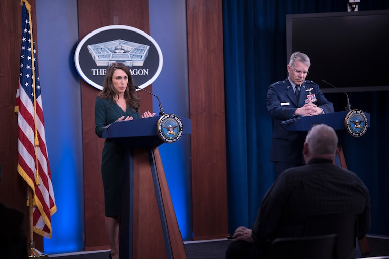 A civilian and an Air Force general stand at lecterns.