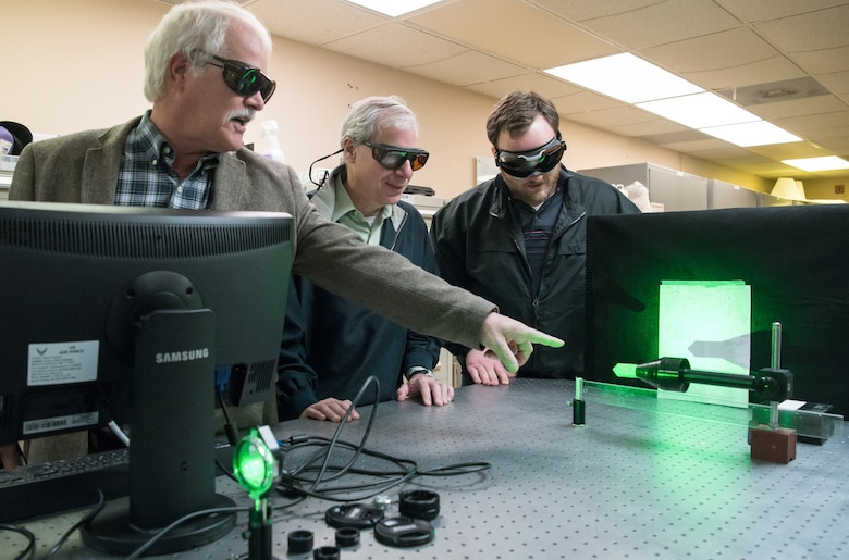 Dr. David Plemmons, left, a senior scientist with the Arnold Engineering Development Complex (AEDC), speaks about the use of a continuous wave laser Jan. 13, 2020, in the Test Technology, Analysis and Evaluation Branch's Laser Laboratory at Arnold Air Force Base, Tenn. The Branch develops measurement and diagnostic techniques utilizing the lasers in the lab that can then be fielded in AEDC test cells.  Also pictured are Dr. Joe Wehrmeyer, center, technical advisor to the Technology Section of the Branch, and Joe Braker, an optical engineer. (U.S. Air Force photo by Jill Pickett)