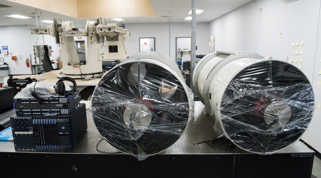 Telescopes, wrapped for shipping, sit on a table in the Optics Laboratory at Arnold Air Force Base, Tenn., Jan. 13, 2020. The telescopes are part of Joint Standard Instrumentation Suite and mount to the platforms in the background. The equipment is in the Optics Laboratory for further development by the Arnold Engineering Development Complex Test Technology, Analysis and Evaluation Branch. (U.S. Air Force photo by Jill Pickett)
