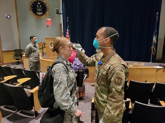 Airman 1st Class Luis Cintron, a dental technician at the Wright-Patterson AFB Medical Center, takes a temperature reading from Capt. Kelsey Pruitt, a nurse practitioner with the Women's Health Center as she arrives for duty March 25. All medical center staff members are now having their temperatures checked upon arriving for duty at the medical center at one specified location. (U.S. Air Force photo/Bryan Ripple)