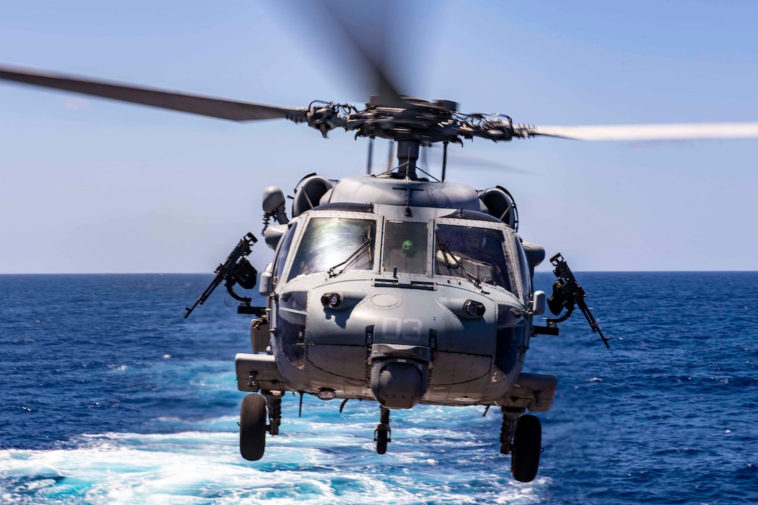 A helicopter flies above blue water.