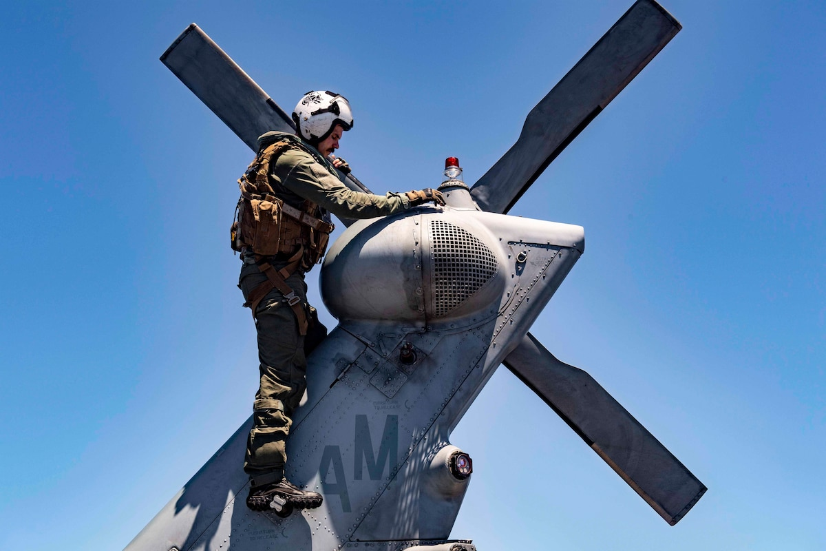 A sailor stands on the tail of a helicopter.
