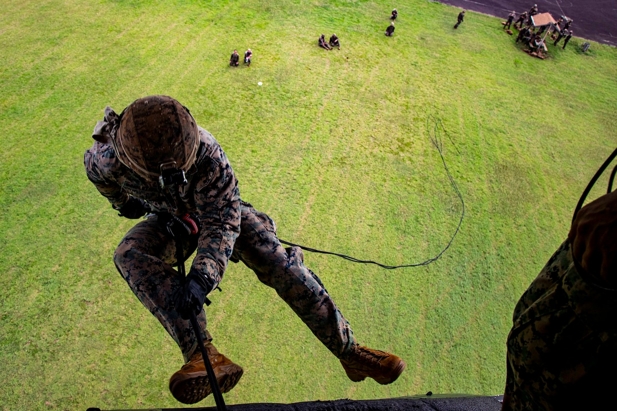 A Marine rappels out of a helicopter; others stand below.