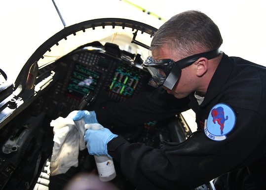 Staff Sgt. Brandon Green, 99th Aircraft Maintenance Unit dedicated crew chief, sprays disinfectant liquid on a rag to sanitize a U-2 Dragon Lady's cockpit Mar. 23, 2020 at Beale Air Force Base, California. The cockpits on Beale's fleet of U-2s will be sanitized on a regular basis to prevent the spread of COVID-19. (U.S. Air Force photo by Airman 1st Class Luis A. Ruiz-Vazquez)