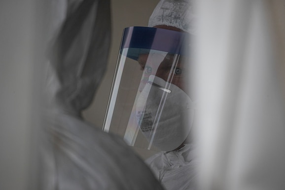 A New Jersey Air National Guard Airman from the 108th Medical Group stands by to assist patients at a COVID-19 Community-Based Testing Site at the PNC Bank Arts Center in Holmdel, N.J., March 23, 2020.  The testing site, established in partnership with the Federal Emergency Management Agency, is staffed by the New Jersey Department of Health, the New Jersey State Police, and the New Jersey National Guard. (U.S. Air National Guard photo by Master Sgt. Matt Hecht)