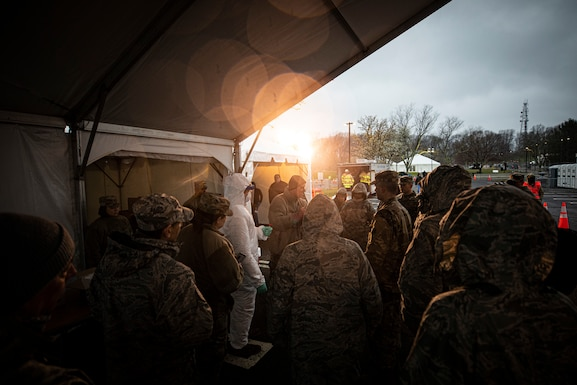 New Jersey Army National Guard Maj. Rory E. Tippit, center, a physician's assistant with the 21st Civil Support Team, demonstrates procedures at a COVID-19 Community-Based Testing Site at the PNC Bank Arts Center in Holmdel, N.J., March 23, 2020.  The testing site, established in partnership with the Federal Emergency Management Agency, is staffed by the New Jersey Department of Health, the New Jersey State Police, and the New Jersey National Guard. (U.S. Air National Guard photo by Master Sgt. Matt Hecht)