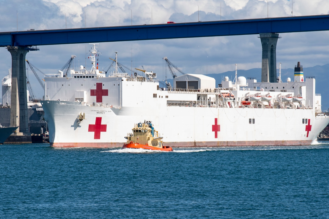 A Navy ship with a red cross on its side is escorted by a small tug boat near a bridge.