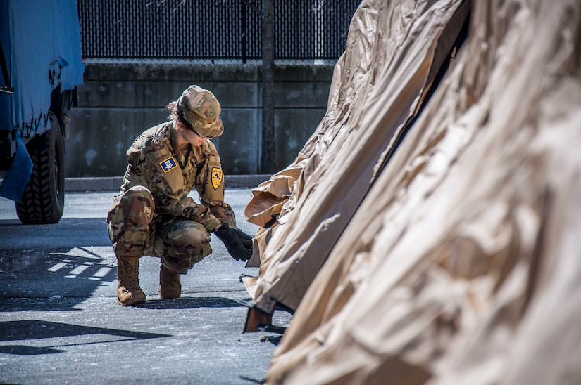 A soldier kneels outside a tent.