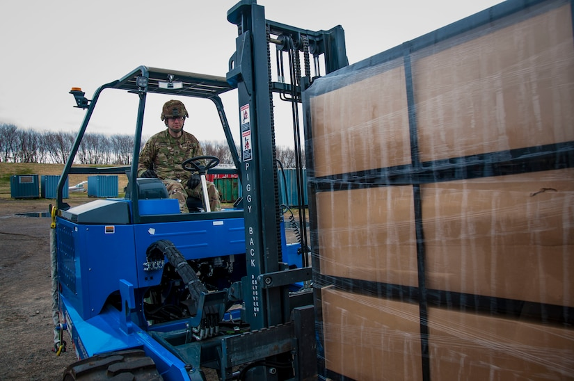 A military member operates a forklift to move a palette of boxes.
