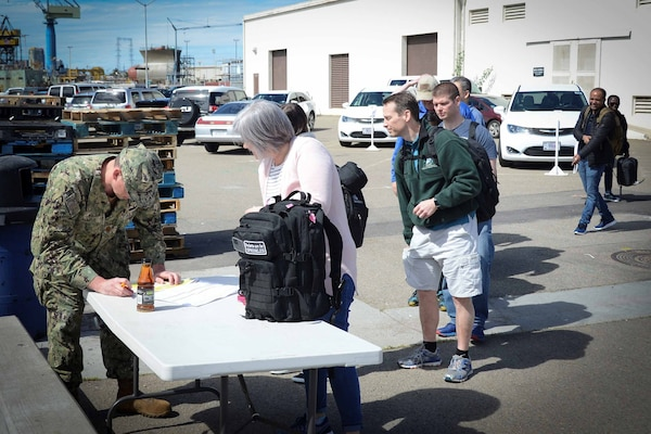 Reservists in civilian clothes line up at a table manned by a sailor in uniform.