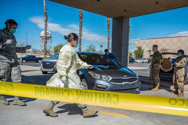 Airmen wearing protective garb gather near a car.
