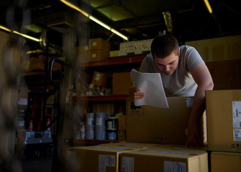An Airmen looks in a box.