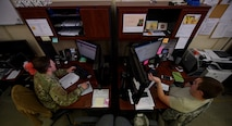 Two Airmen sit at their desk.